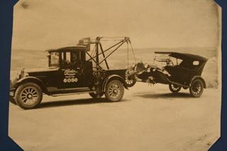 Al remolque de un Ford T con la llanta de madera destrozada.